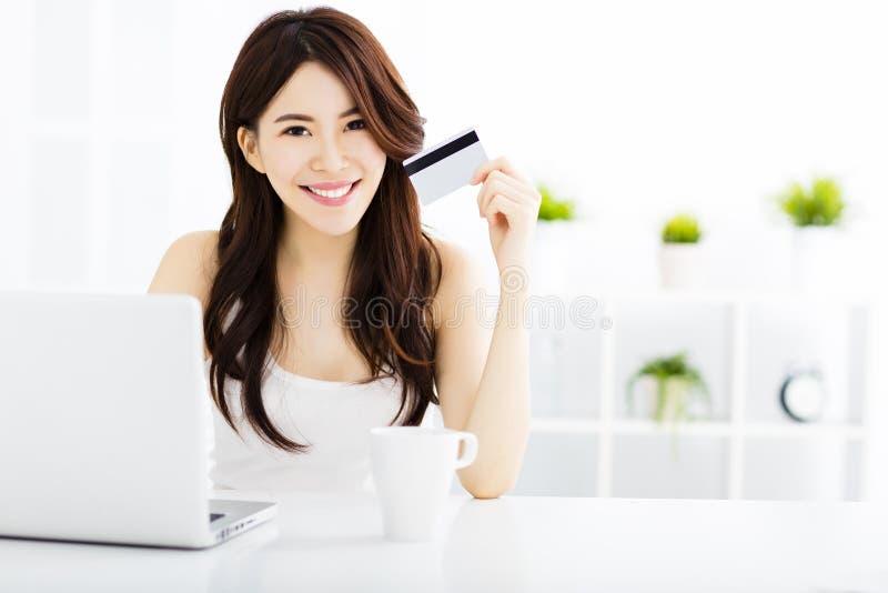 Acquisto della giovane donna online e carta di credito di rappresentazione immagini stock