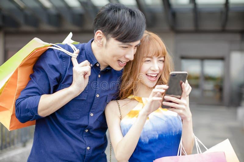 Acquisto delle coppie con lo Smart Phone in centro commerciale immagini stock