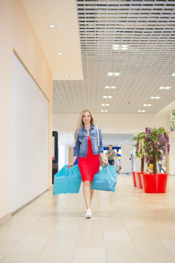 Acquisto di concetto Il ritratto della donna sorridente bionda di bellezza in sacchetti della spesa casuali della tenuta vicino c immagine stock