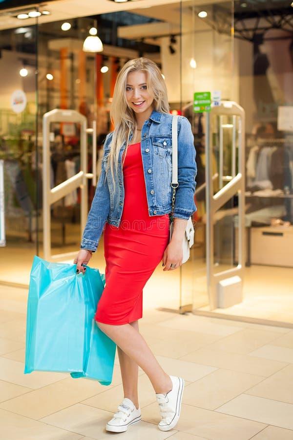 Acquisto di concetto Il ritratto della donna sorridente bionda di bellezza in sacchetti della spesa casuali della tenuta vicino c fotografia stock libera da diritti