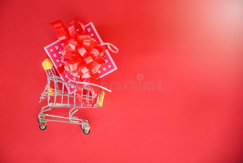 Acquisto di giorno di biglietti di S. Valentino e scatola attuale di rosa del contenitore di regalo con l'arco rosso del nastro s immagine stock libera da diritti