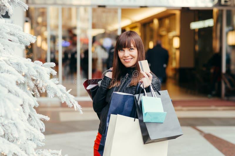 Acquisto di natale, idea per il vostro disegno Bella ragazza felice con la carta di credito in Sho fotografie stock