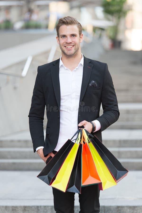 Acquisto esclusivo Il cliente dell'uomo porta il fondo urbano dei sacchetti della spesa L'uomo d'affari riuscito sceglie soltanto fotografia stock