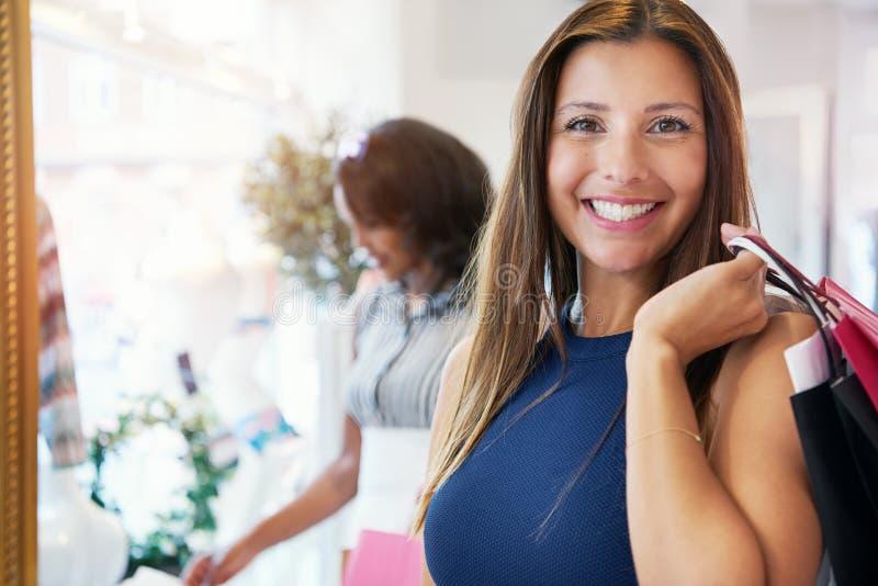Acquisto felice attraente della giovane donna per i vestiti fotografia stock libera da diritti