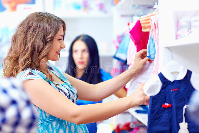 Acquisto felice della donna incinta nel deposito del bambino fotografia stock libera da diritti