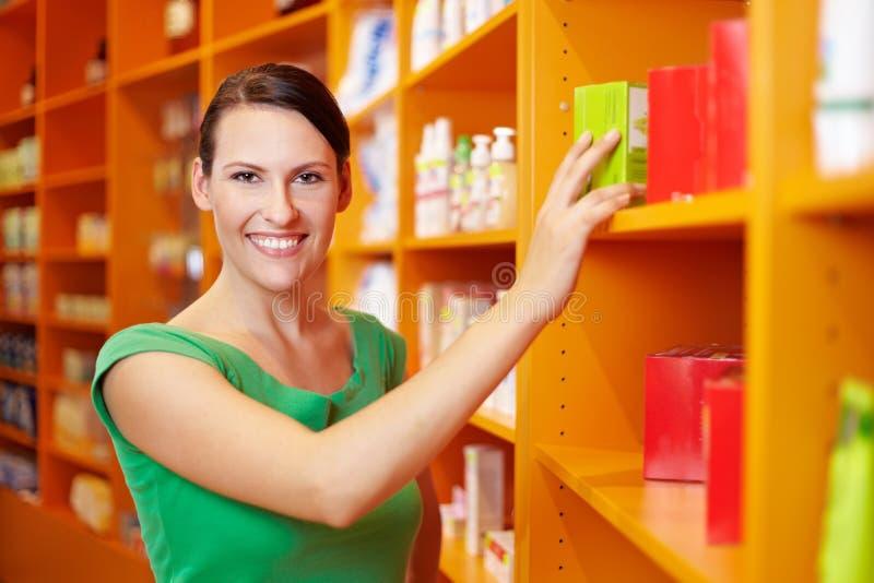 Acquisto felice della donna nella farmacia immagine stock