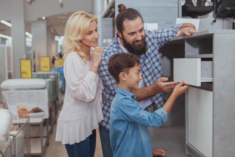 Acquisto felice della famiglia al negozio di mobili fotografie stock