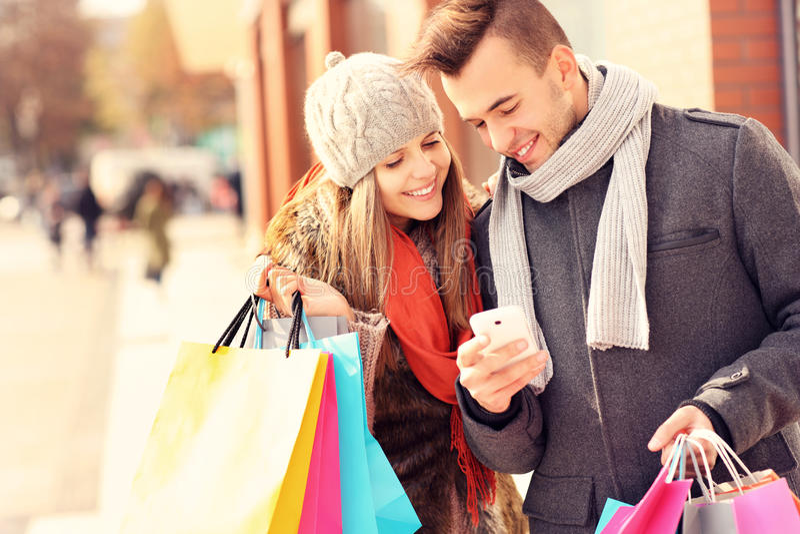 Acquisto felice delle coppie nella città con lo smartphone fotografie stock