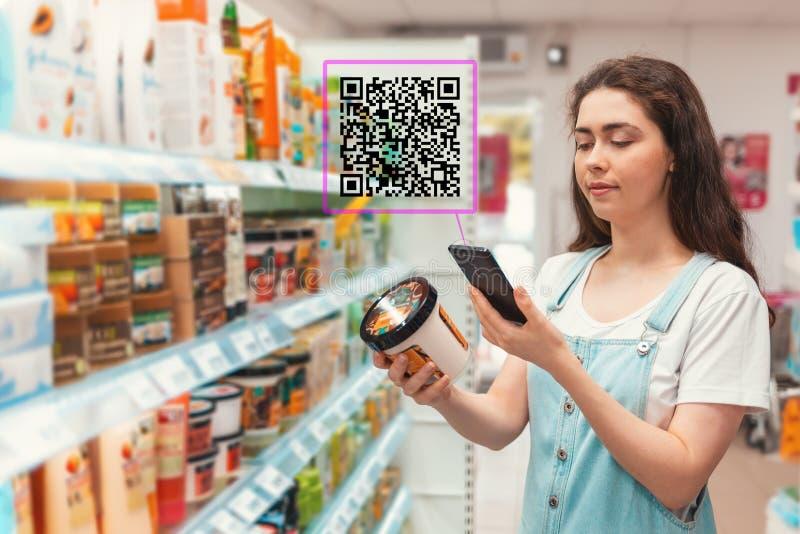 Acquisto Giovane bella pubblicità della crema per il corpo di esame della donna con il codice rapido di risposta sullo smartphone fotografie stock libere da diritti