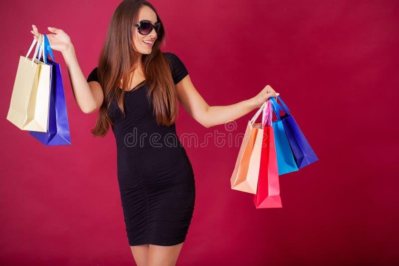 Acquisto Giovane donna graziosa vestita alla moda nel nero con le borse dopo la compera immagine stock