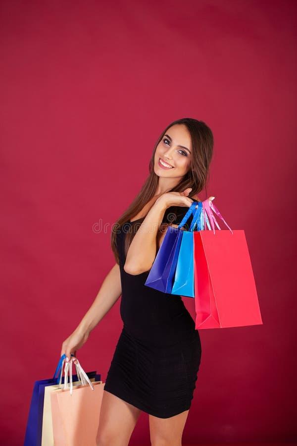 Acquisto Giovane donna graziosa vestita alla moda nel nero con le borse dopo la compera immagini stock libere da diritti