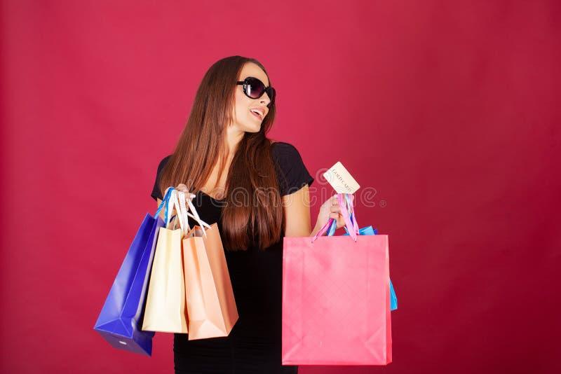 Acquisto Giovane donna graziosa vestita alla moda nel nero con le borse dopo la compera immagini stock