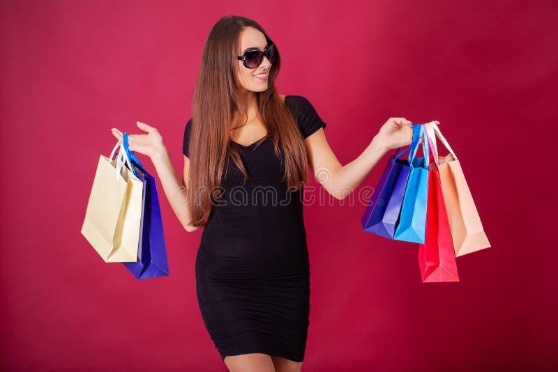 Acquisto Giovane donna graziosa vestita alla moda nel nero con le borse dopo la compera fotografie stock