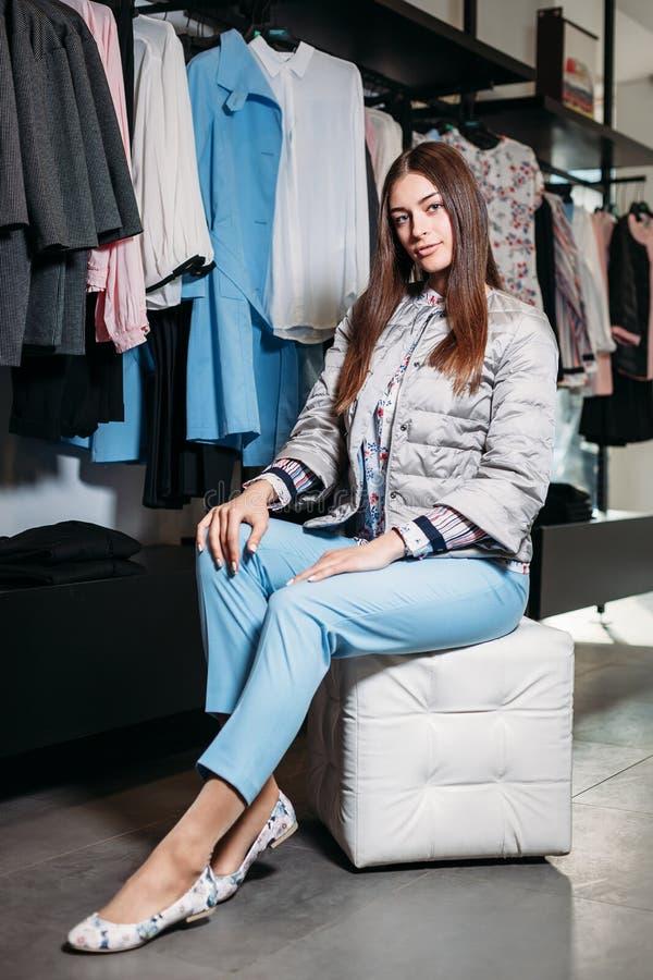 Acquisto, modo, stile, vendita, acquisto, affare e la gente bella giovane donna felice di concetto in negozio di vestiti Affare fotografia stock