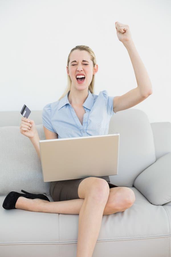 Acquisto online incoraggiante attraente della donna di affari con il suo computer portatile fotografia stock