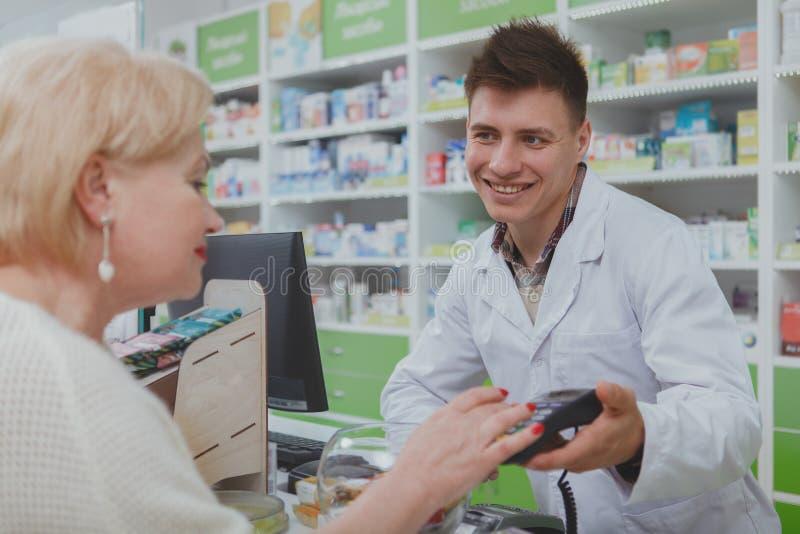 Acquisto senior adorabile della donna alla farmacia immagini stock