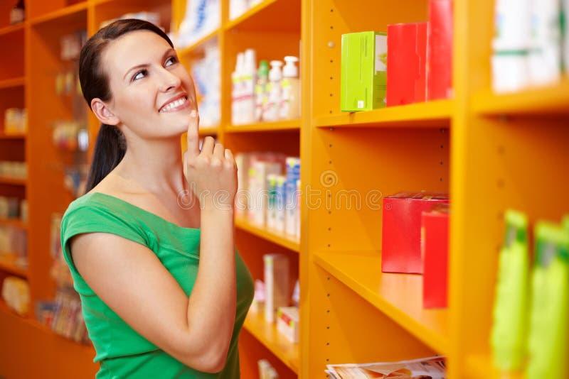 Acquisto soddisfatto della donna nella farmacia immagini stock