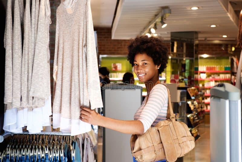 Acquisto sorridente della donna nel negozio di vestiti immagini stock libere da diritti