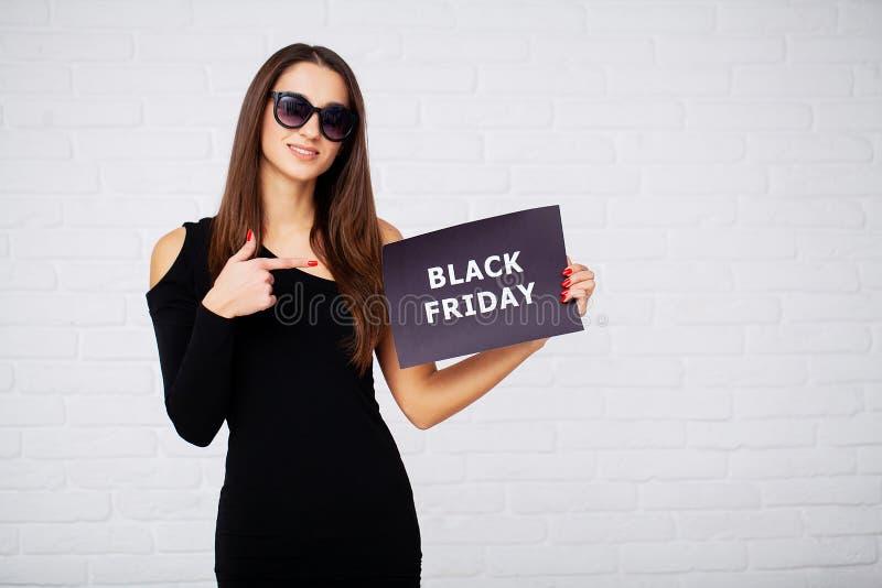 Acquisto Spazii in bianco del holdingdiscount delle donne sul fondo del ligth nella festa nera di venerdì immagini stock libere da diritti