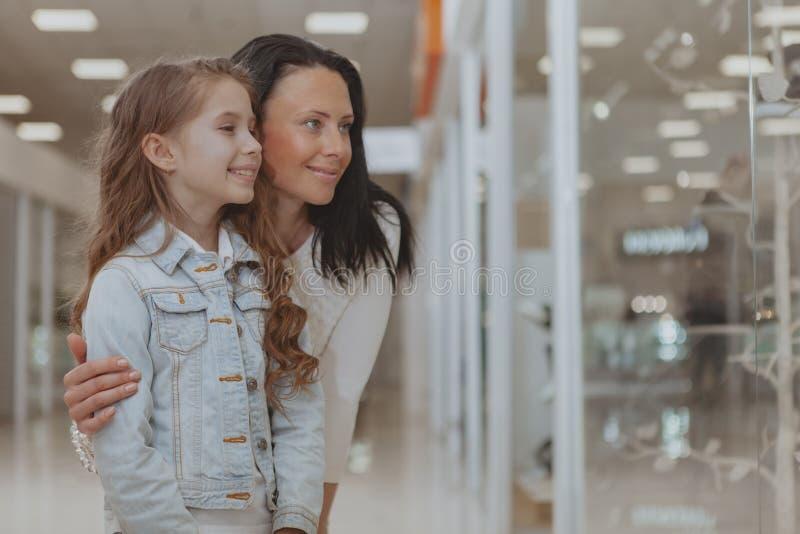 Acquisto sveglio della bambina al centro commerciale con sua madre fotografia stock libera da diritti