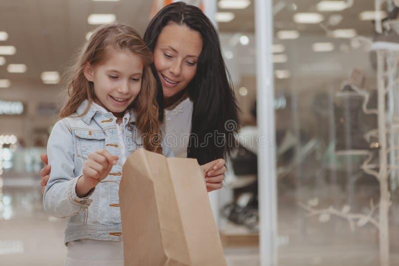 Acquisto sveglio della bambina al centro commerciale con sua madre immagine stock libera da diritti