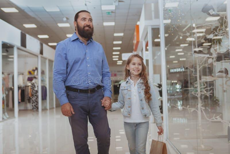 Acquisto sveglio della bambina al centro commerciale con suo padre immagini stock libere da diritti