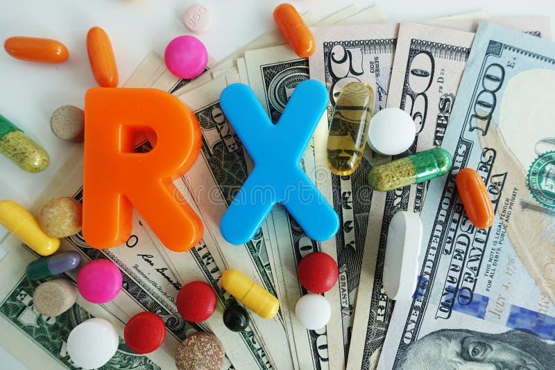 Acrônimo de RX dos comprimidos médicos coloridos no dinheiro dólares americanos foto de stock royalty free