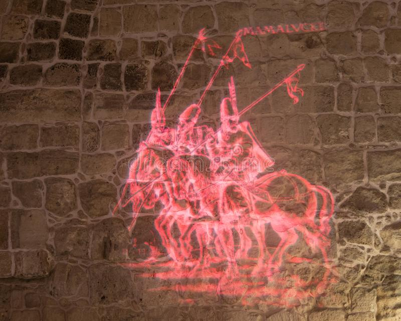 Light projecting tells about the time of the Turkish conquest on the inner wall of the hall in the ruins of the fortress in the ol royalty free stock photography