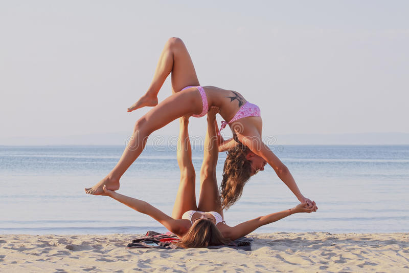 Acro yoga. Beautiful girls performing an advanced acro yoga balance at the sea coast of Sozopol,Bulgaria royalty free stock image