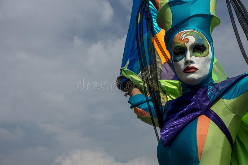 Acrobat in colorful mask in the blue sky royalty free stock photography