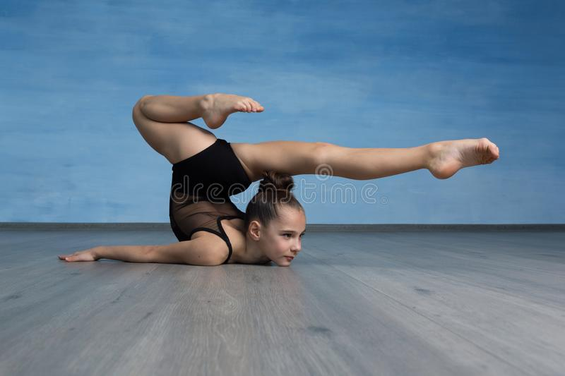 Acrobat standing in back bend pose on blue background. stock photography