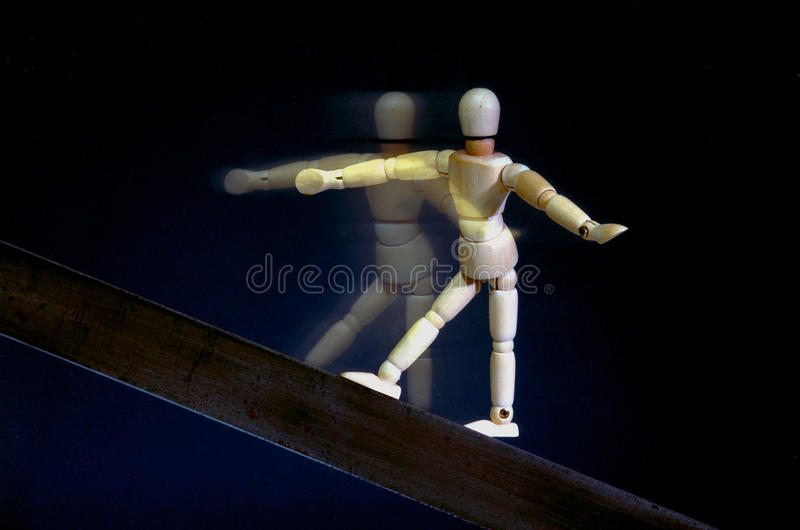 Acrobat. A wooden mannequin walking on a metal board as an acrobat on a black background royalty free stock photography