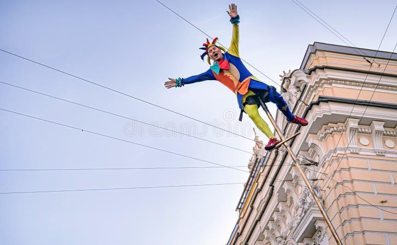 Acrobate de clown de cirque balançant sur un long poteau photos libres de droits