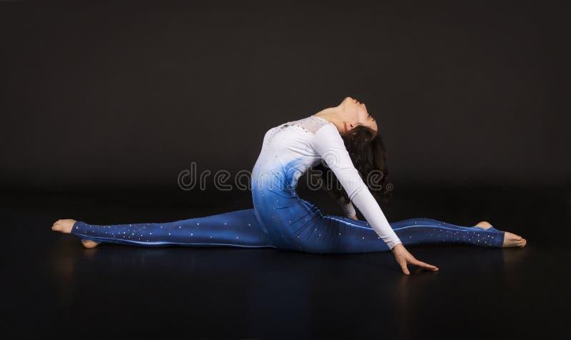 Acrobate de fille, gymnastique, un jeune athl?te dans un costume bleu et blanc, acrobaties de pratique Images d'isolement sur le  images libres de droits