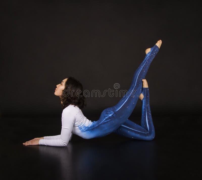 Acrobate de fille, gymnastique, un jeune athl?te dans un costume bleu et blanc, acrobaties de pratique Images d'isolement sur le  images stock