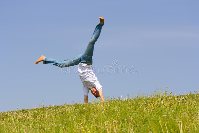 Acrobatic feat. Young girl do acrobatic feat on the flank of hill royalty free stock images
