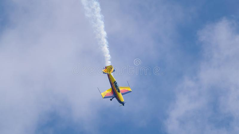 An acrobatic plane, flying in the blue sky with white clouds, doing acrobatics royalty free stock image