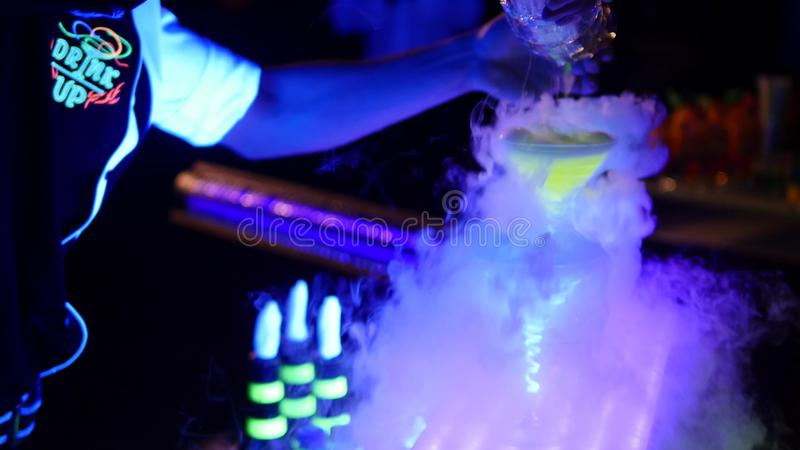 Acrobatic show barman performing exhibition move at night club - Concept of freestyle american bartending in action -. Bartender at working in disco party stock photography