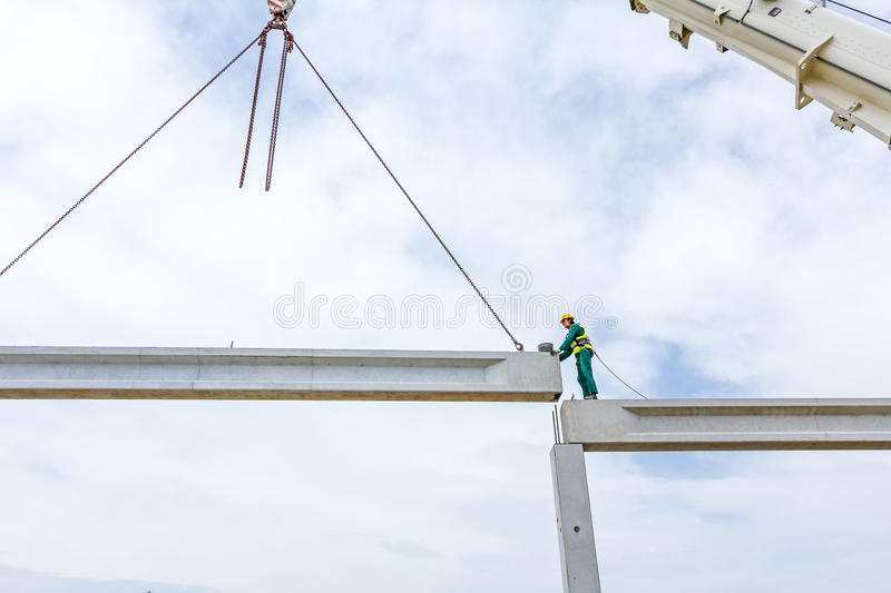 Acrobatic way of assembly concrete joist. Placing the truss on b royalty free stock photography