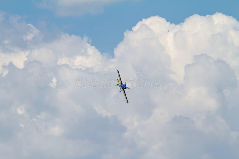 Acrobatisch vliegtuig op bewolkte hemel stock afbeeldingen