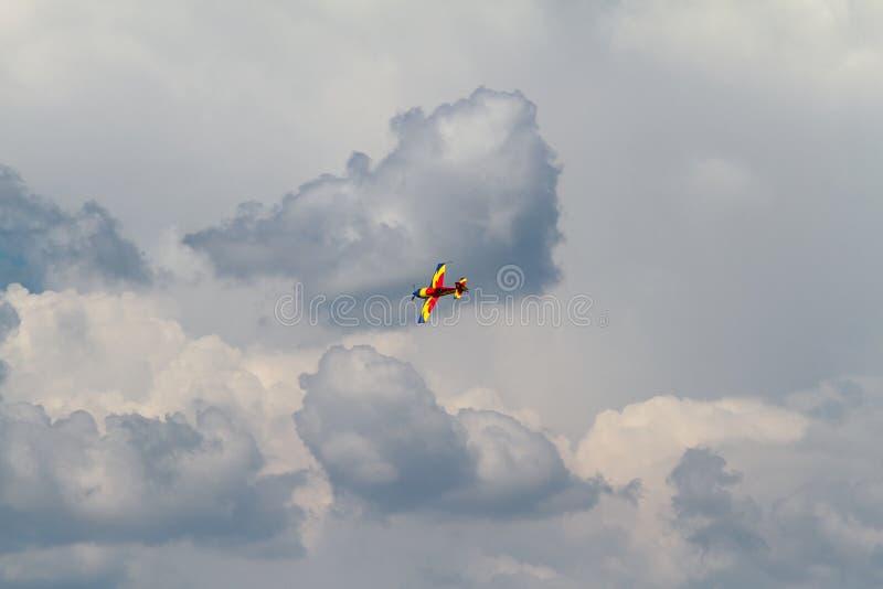 Acrobatisch vliegtuig op donkere wolken stock foto
