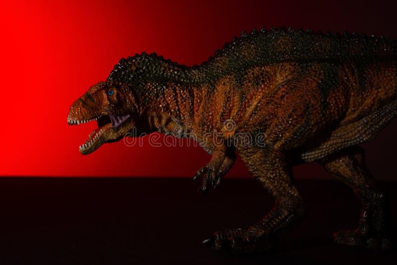 Acrocanthosaurus med fläckljus på huvudet och röda ljuset på bakgrund royaltyfri bild
