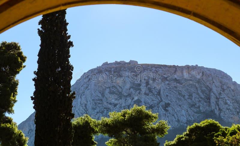 Acrocorinth eller övreCorinth - ett monolitiskt vagga kontroll av den forntida staden av Corinth Grekland - som beskådas till och arkivfoton
