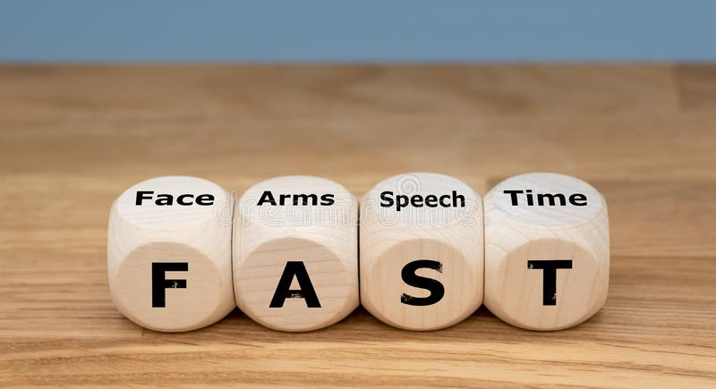 The acronym FAST on cubes. The acronym `FAST` is used as mnemonic to help a person having a stroke. `FAST` stands for `facial drooping`, `arm weakness`, `speech royalty free stock images