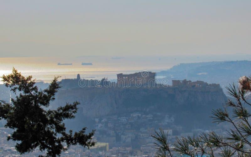 Acropoli con il panteon, le costruzioni bianche architettura, la montagna, gli alberi ed il tramonto dorato del mare a Atene immagine stock