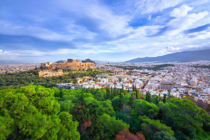 Acropoli con il Partenone Vista attraverso una struttura con le piante verdi, gli alberi, i marmi antichi ed il paesaggio urbano, fotografie stock