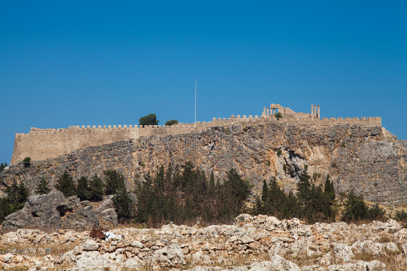 Acropolis on a hill in the city of Lindos. Fragment of residential buildings at the foot of the mountain. royalty free stock image