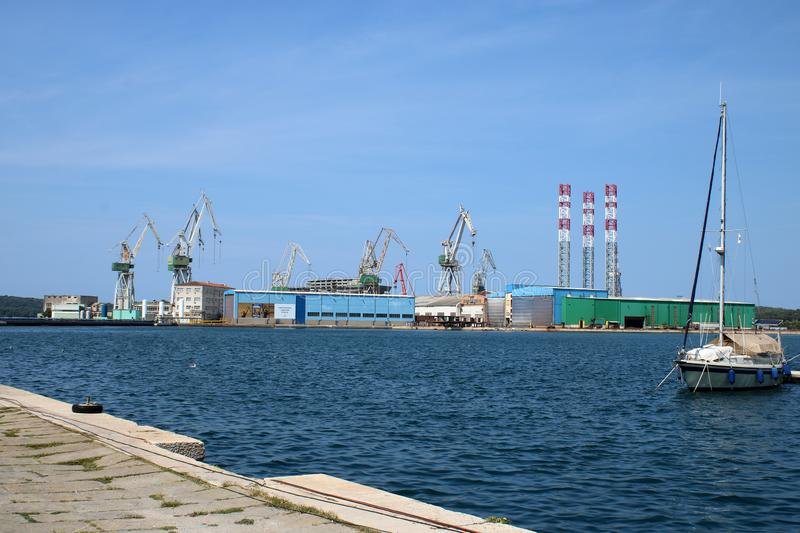 Across Pula harbor to dockyard cranes, Croatia. View across the open water in Pula harbor to the giant dockyard cranes and other assorted buildings on the far royalty free stock images