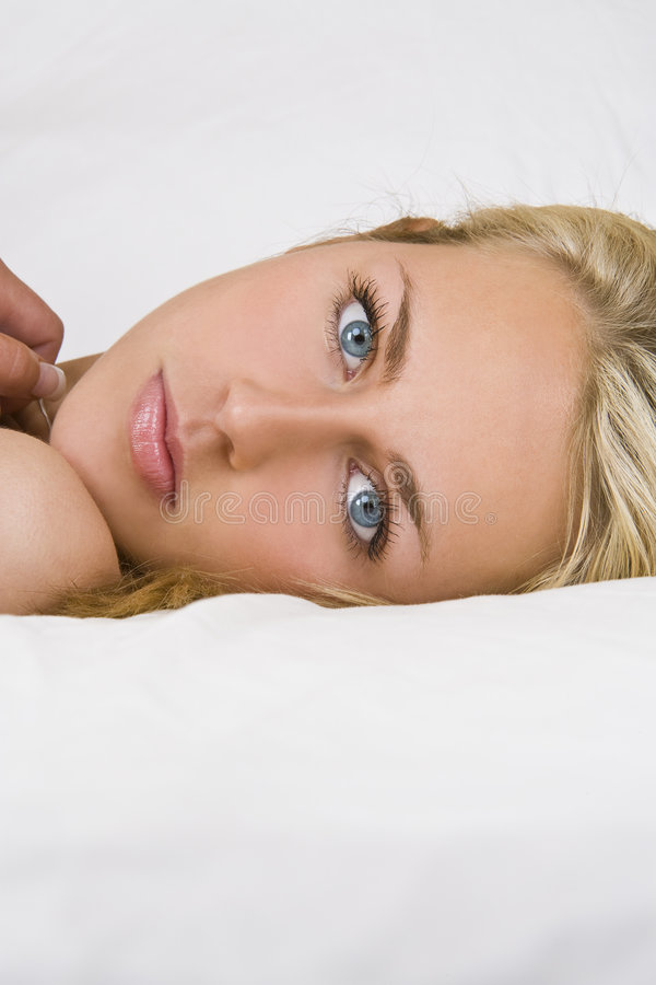 Across The Sheets. A beautiful blond haired blue eyed young woman laying on white sheets and looking into the camera royalty free stock photo