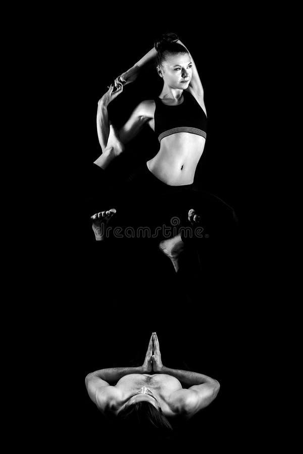 Acroyoga Yoga di pratica di acro delle giovani coppie sulla stuoia in studio insieme Yoga delle coppie Yoga del partner Foto in b immagine stock libera da diritti